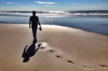 man walking at seashore